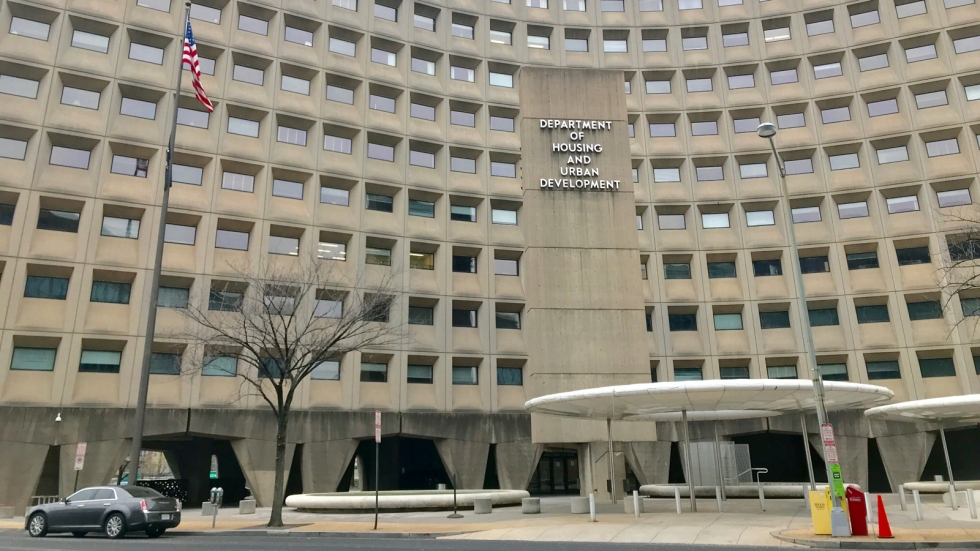 """A large concrete building with glass building. A sign in front says """"Department of Housing and Urban Development."""""""