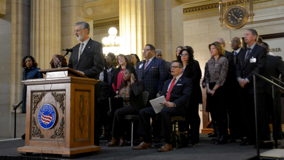 Cleveland Mayor Frank Jackson at a podium surrounded by a coalition to support the city's lead safe plan. [Nick Castele / ideastream]