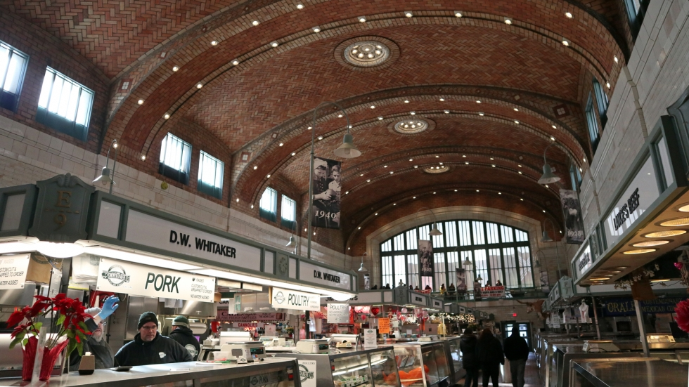 A shot of the interior of the West Side Market. A vendor selling meats is on the left, a row of empty stalls on the right. The ceiling is very high and curved.