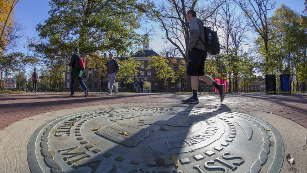 A student walks across the seal of Miami University in Oxford, Ohio.