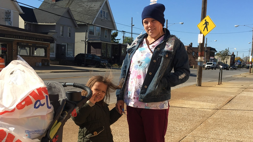 Megan McKnight stands with her daughter on Clark Avenue in Cleveland.