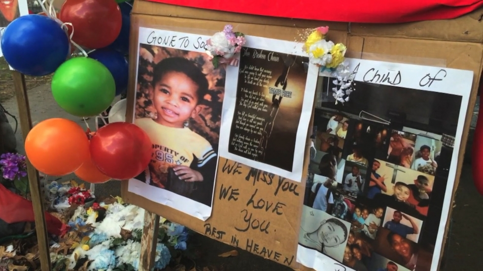 A poster memorializing Tamir Rice with childhood photos and balloons