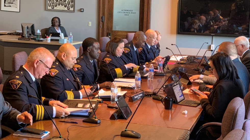Members of the police department sit across from the city's safety committee in the council meeting room.