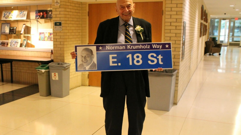 Norman Krumholz holds a street marker that was posted to honor his 90th birthday in 2017