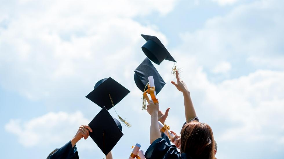 Four students in graduation gowns throwing their caps in the air