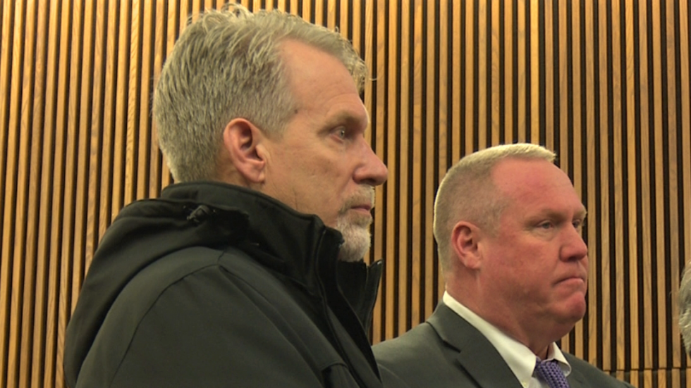 Former Cuyahoga County jail director Kenneth Mills (left) stood with his attorney Kevin Spellacy to plead not guilty.