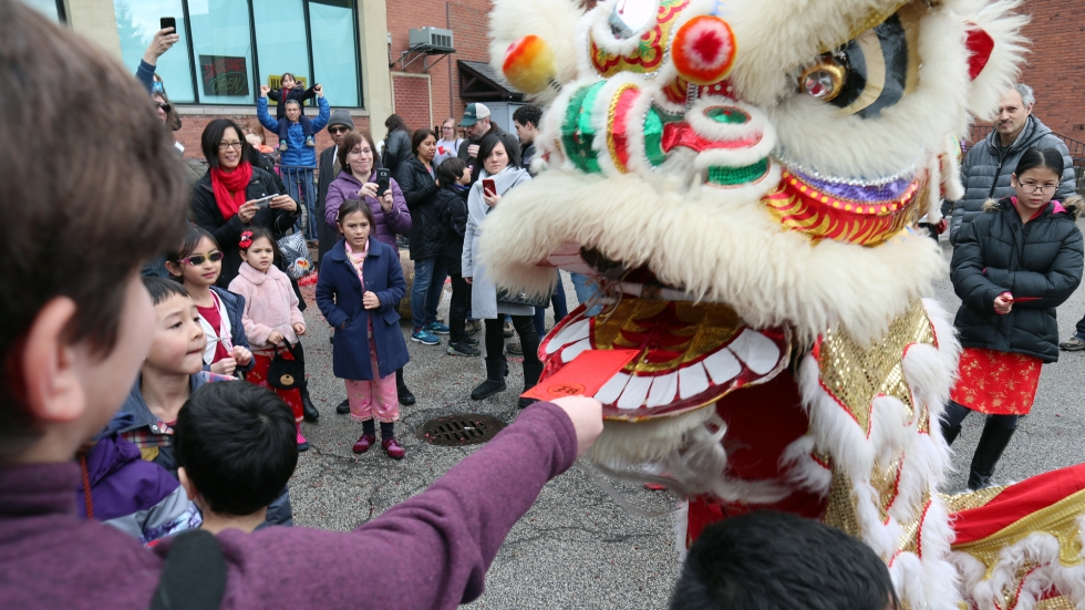 "A child holds a red envelope of ""lucky money"" up to the jaws of a rainbow-colored lion, really, a costume played by two performers."