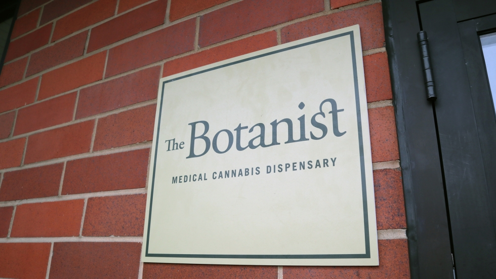 A square, yellowish sign with black letters against a brick wall. It reads The Botanist, Medical Cannabis Dispensary