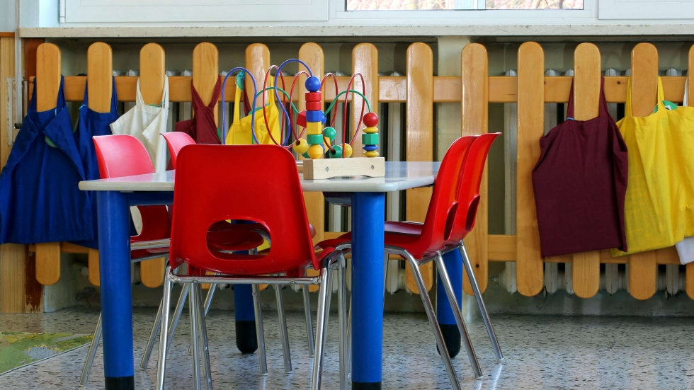 Stock photo of a preschool room with children's table, chairs and toys