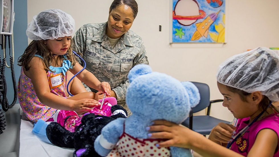 Air Force Senior Airman Antoinette Fowler shows a 4-year-old how to give a vaccination during a teddy bear clinic at Eglin Air Force Base, Florida.  The event taught children about the importance of vaccination and immunization.