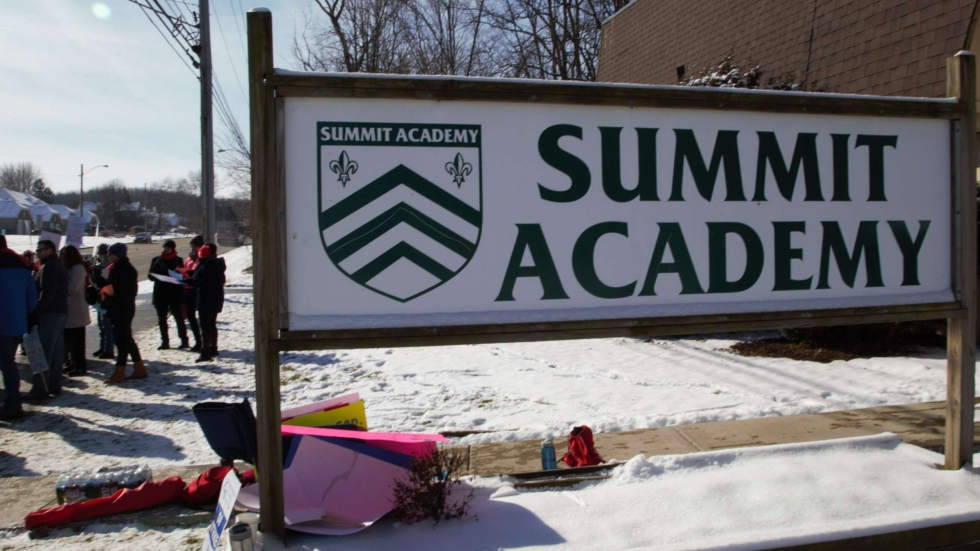 On the sidewalk behind the Summit Academy sign, teachers picket outside the charter school Tuesday.