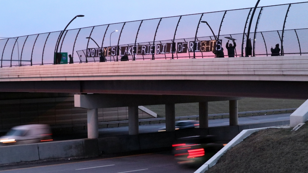 "A highway overpass stretches from the left to the right of the picture. The sun is setting in the background. On the bridge, a dozen people are putting up letters that spell out the message ""Vote Yes, Lake Erie Bill of Rights."""