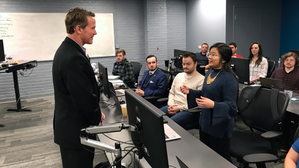A man in a black suit stands before a classroom. In front of him a young woman with glasses is standing and talking.