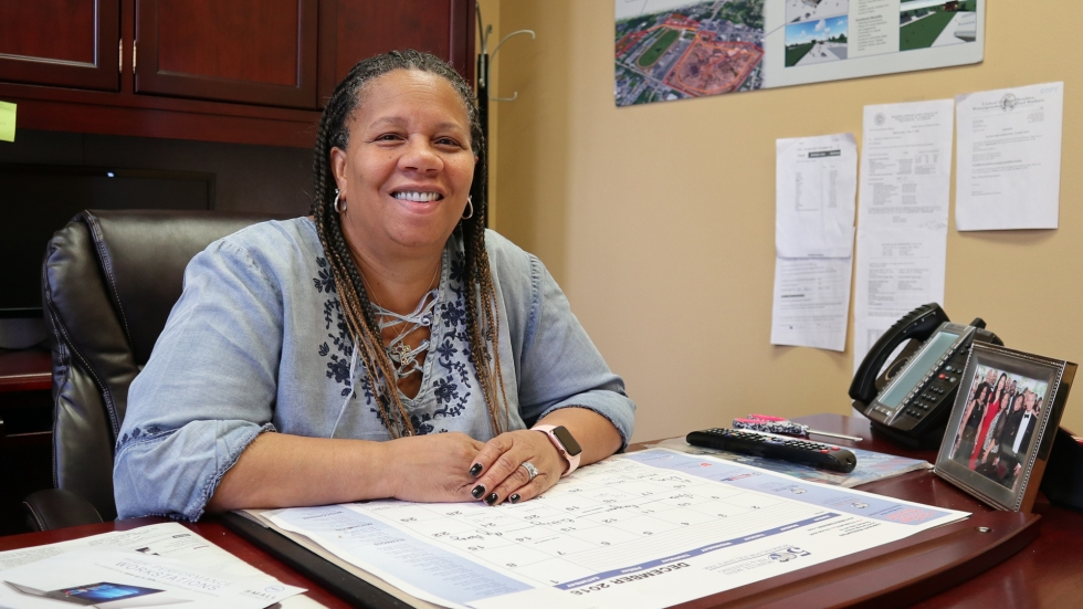 A woman with braids and a blue smoke is sitting between her wooden desk in an office. She is smiling and looking at the camera.
