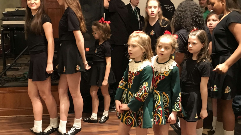 Young girls in costume wait with other students of the Burke School of Irish Dance to perform at the Sober Seventeenth St. Patrick's Day event at Ahern's Banquet Center in Avon Lake, March 17, 2019. [Amy Eddings / ideastream]