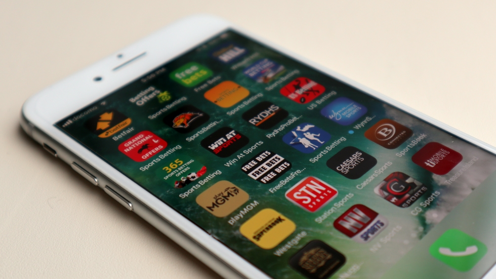 A white iPhone lays on a table. The screen shows several rows of sports betting apps.