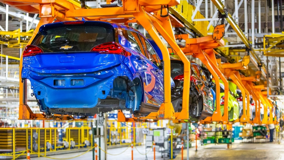 The body of a blue, half-assembled car hangs from a series of brackets in a large assembly plant.