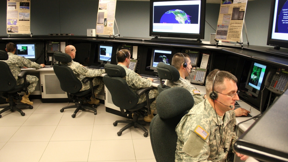 Five men in army camouflage sit in a semi-circle, each at computer terminals, and screens overhead that show the earth.