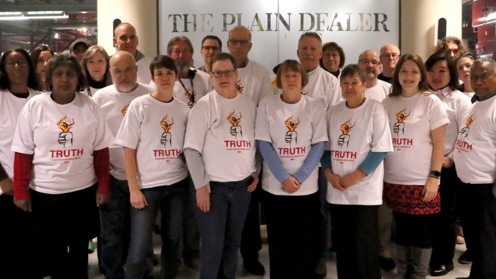 Members of Northeast Ohio Newspaper Guild, Local 1 members stand in front of the Plain Dealer sign at the newspaper's office.