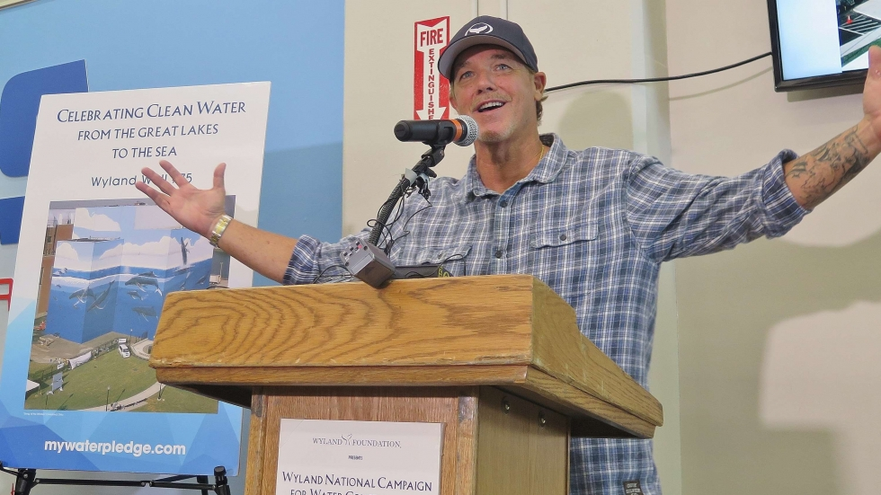 Muralist Wyland at a podium announcing his foundation's water conservation challenge.