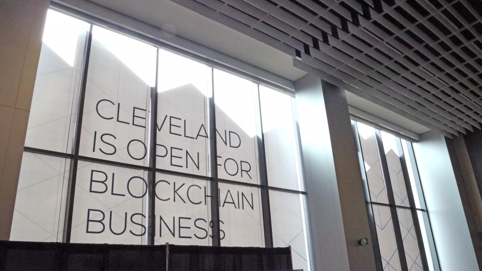 "A window display at the Blockland Solutions Conference in Cleveland this past December. Large rectangular windows stretch from floor to ceiling, and a sign with large block letters reads ""CLEVELAND IS OPEN FOR BLOCKCHAIN BUSINESS""."