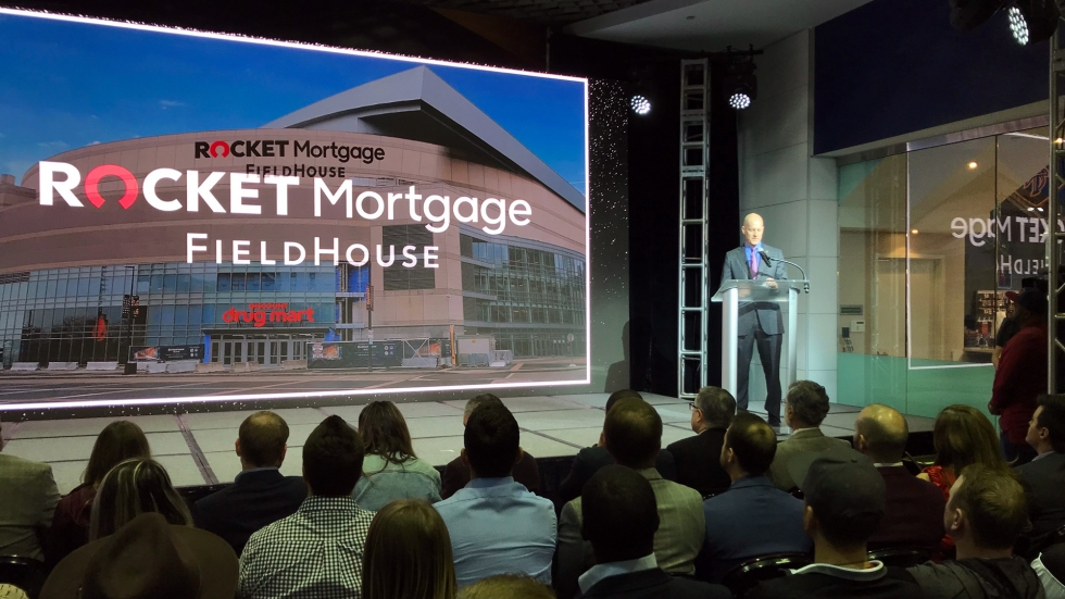 """A large screen displays the exterior of a larger arena, with the words """"Rocket Mortgage FieldHouse"""" superimposed on it. A man stands at a podium to the right of the picture. He's standing on a stage before of a couple of dozen people seated in front of him."""