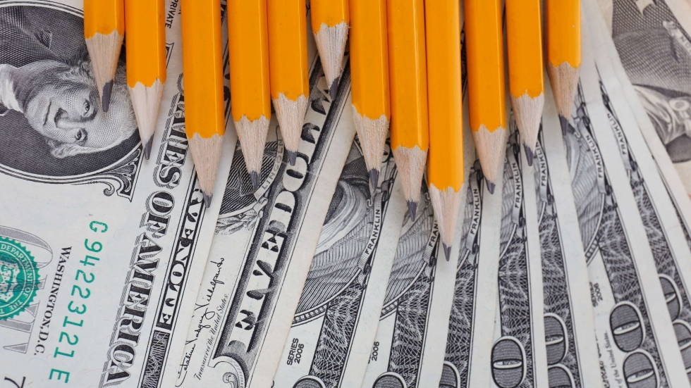 A stock photo of 100 dollar bills and pencils