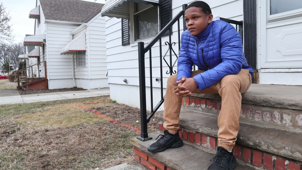 Ricco Williams sits on the stoop of his family's home in Euclid.