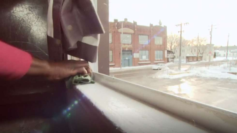 A woman wipes down a windowsill in her home. Windows can be a source of lead paint chips or dust.