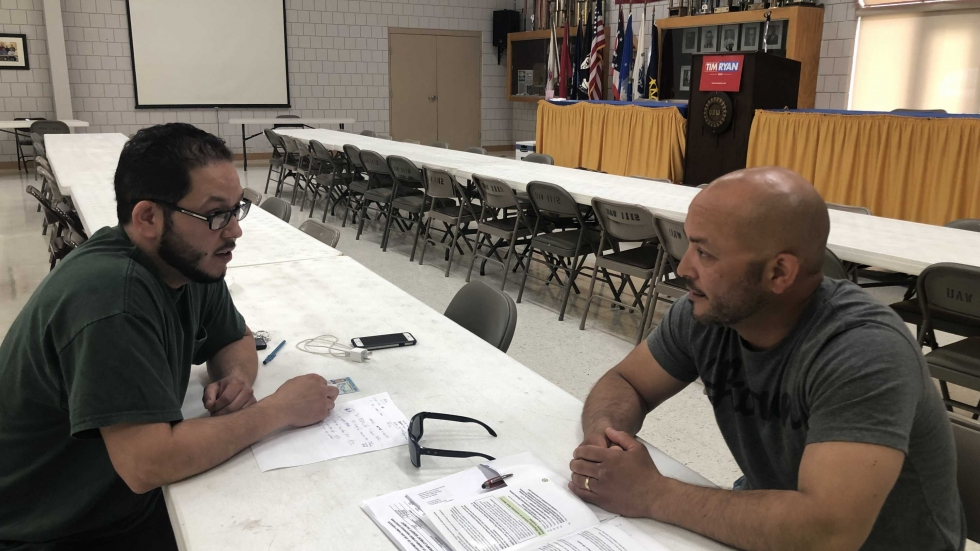 Two Lordstown GM workers are sitting at a table at the UAW Local 1112 headquarters.
