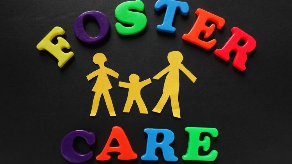 Foster care spelled out in toy magnetic letters with a cut out image of a family. Demand for foster care services is part of the reason that the Cuyahoga County Health and Human Services Department is running a multi-million dollar deficit.