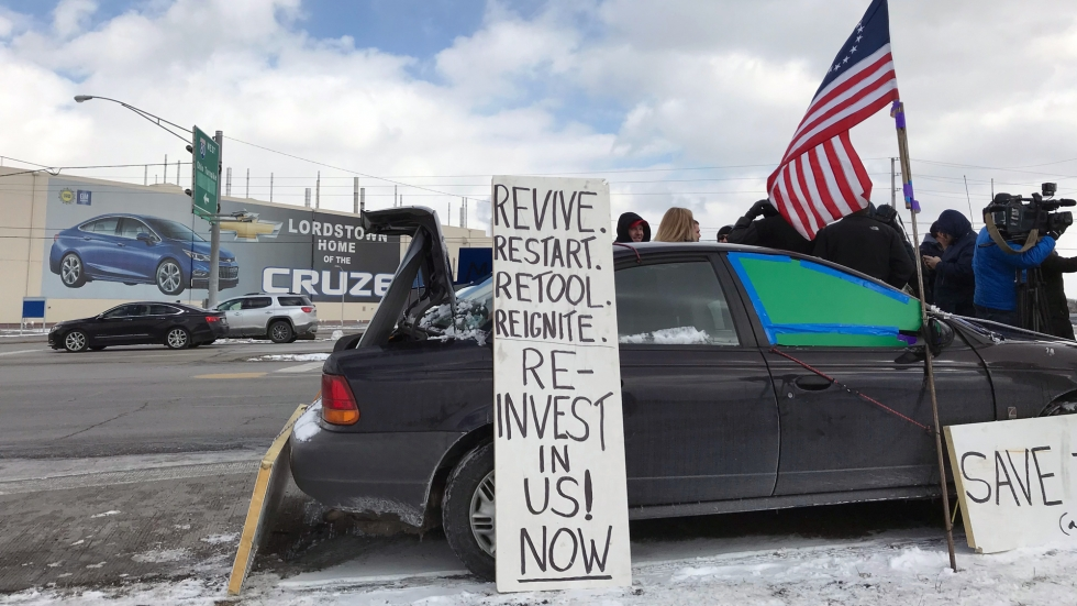 "A sign reading, ""Revive. Restart. Retool. Reignite. Reinvest in US! Now"" leans against a car beside an American flag outside the GM Lordstown plant."
