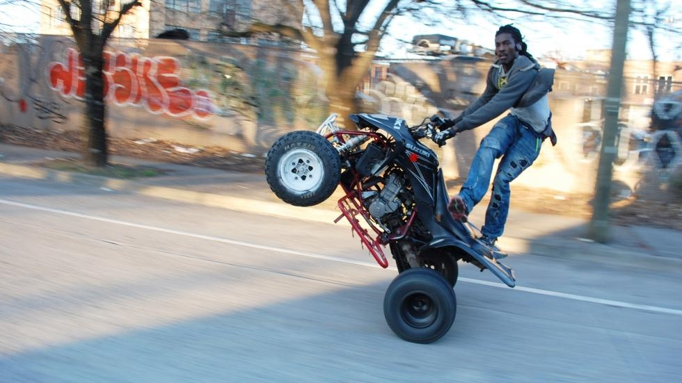 An ATL Bike Life rider pops a wheelie on an Atlanta street in 2017.