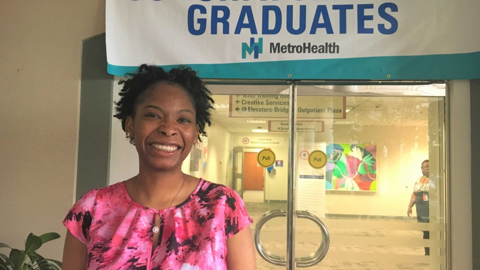 Endia Reynolds is among the first graduating class at Lincoln-West School of Science and Health at MetroHealth. She is standing in front of a sign that reads congratulations graduates.
