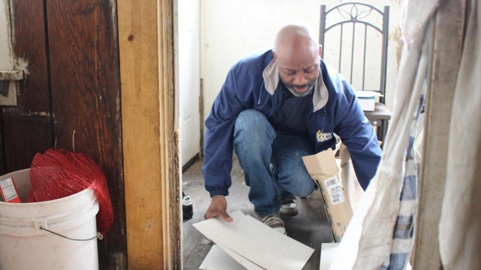 Akbar Tyler, a home inspector with Environmental Health Watch, puts tile over the peeling lead paint on a back porch in 2015.