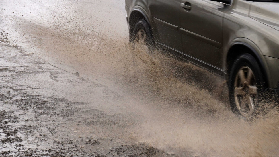 A car quickly goes on a puddle throwing out splashes and water from under wheels.