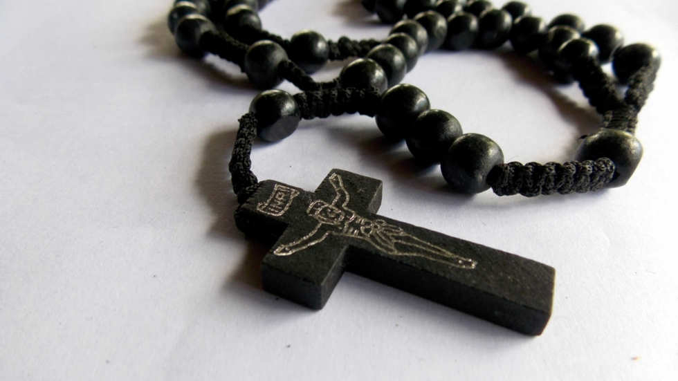 Catholic rosary beads and cross on a white background