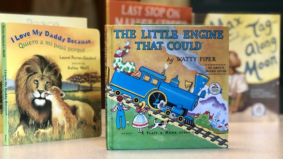 The Little Engine That Could is the first book children receive as a part of the Dolly Parton Imagination Library. That book is among several others on a table.