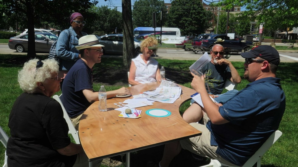 A table of people discuss the new Shaker Square design plan on the lawn beside Shaker Blvd.