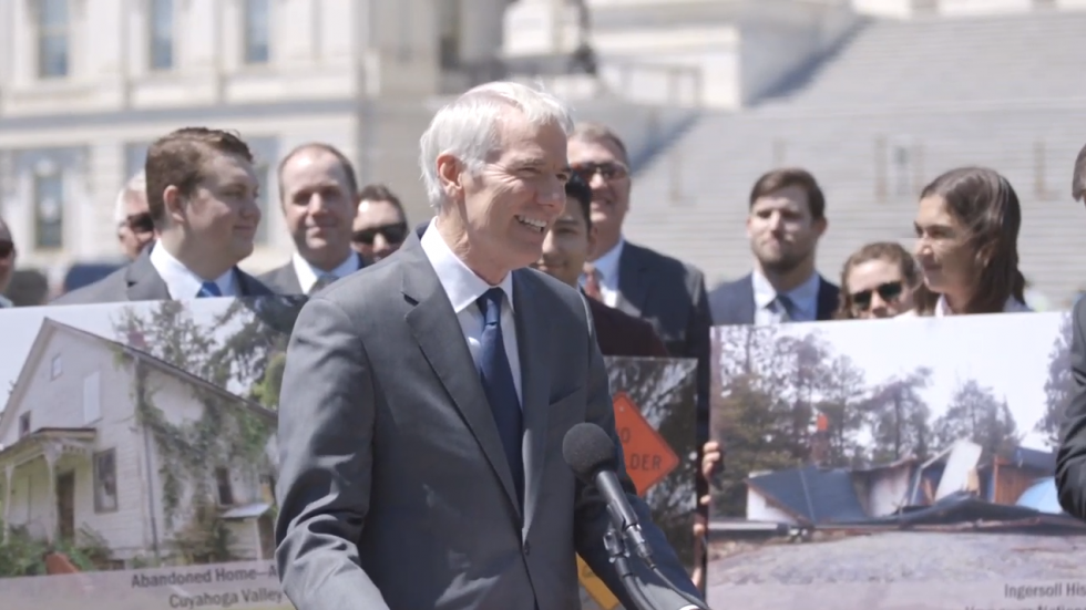 Sen. Rob Portman (R-OH) at a May press conference promoting the Restore Our Parks Act stands in front of a photo of a house awaiting demolition in the Cuyahoga Valley National Park.