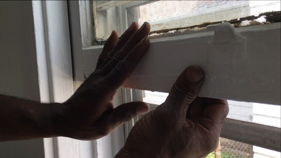 Akbar Tyler of Environmental Health Watch demonstrates how painted windows can be a source of lead hazards