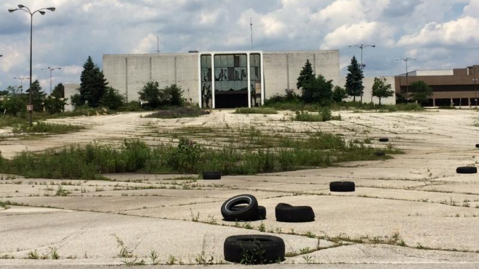 A vacant store and a weedy, tire-strewn parking lot at the former Rolling Acres Mall in Akron will be redeveloped into a four-story Amazon fulfillment center. [Khabir Bhatia / WKSU]