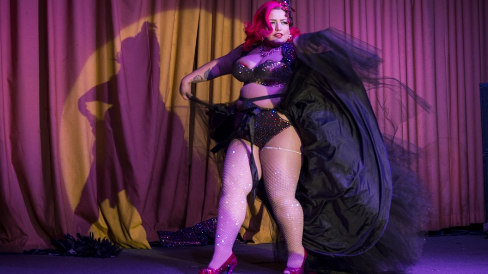 Burlesque performer Bella Sin in on stage in elaborate feathered costume
