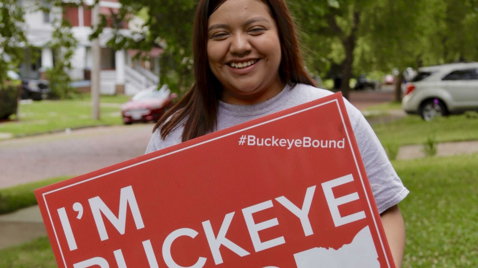 Mariyln Macario holds an Ohio State University sign in her front yard as she prepares to head to college thanks to Say Yes To Education Tuition Assistance.