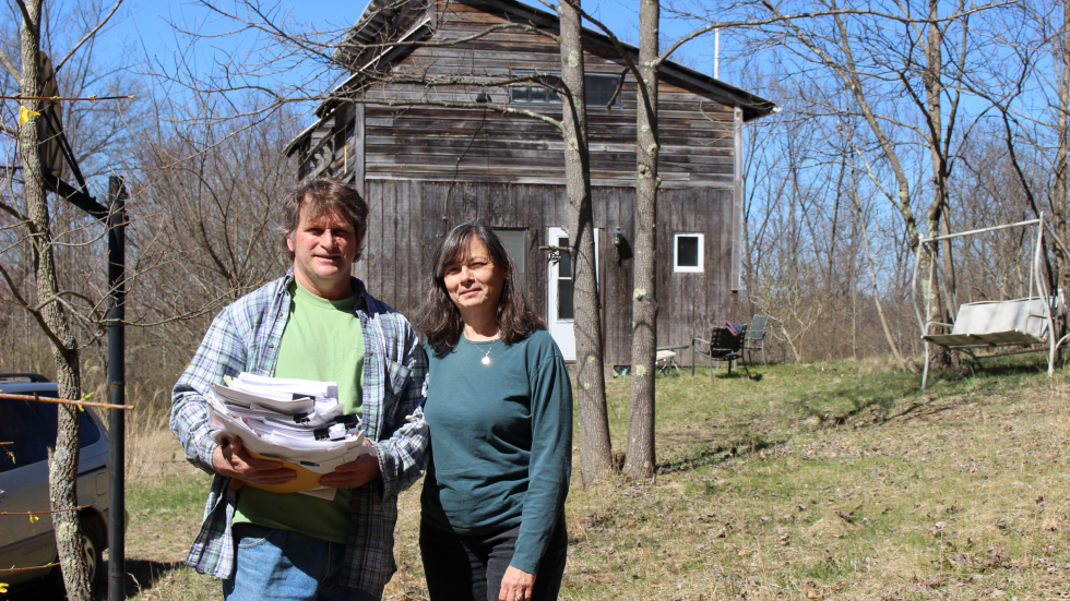 Patrick Hunkler and Jean Backs in front of their house, with the paperwork for their unitization case. [Julie Grant / The Allegheny Front]