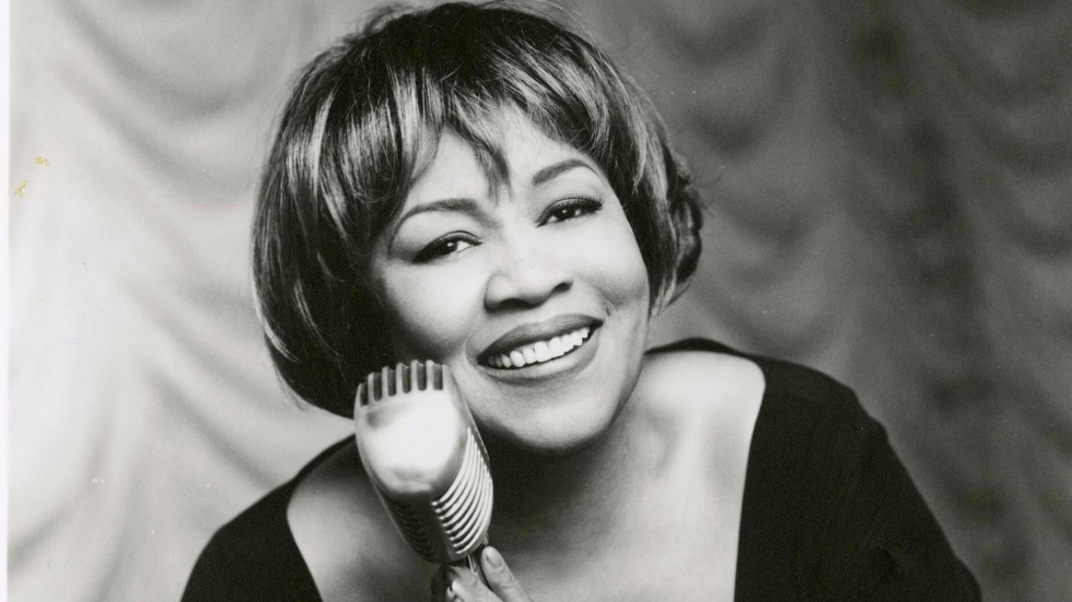 Mavis Staples in a publicity shot with Mavis crooning into a vintage microphone for her early 1990s collaborations with Prince