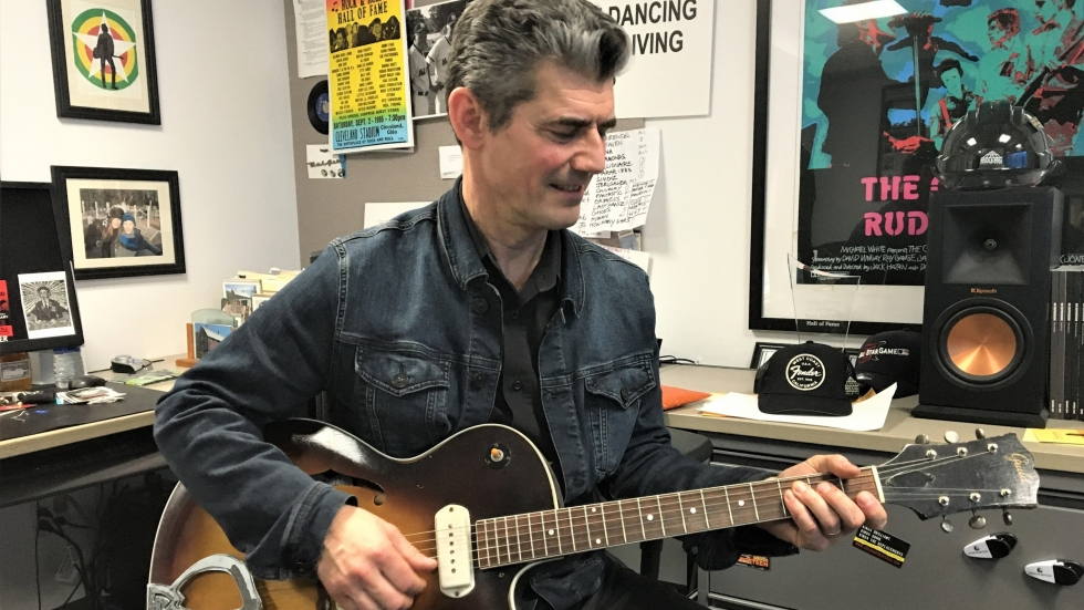 Rock Hall CEO Greg Harris strums a well-worn guitar in his office. A quiet moment in advance of a busy year.
