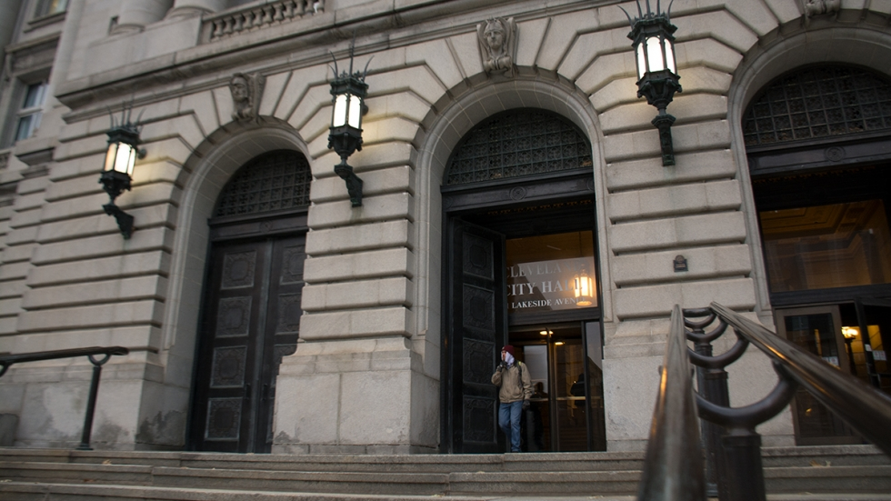 A man leaves Cleveland City Hall in December. Voters will decide in March whether to cut council's membership and pay.