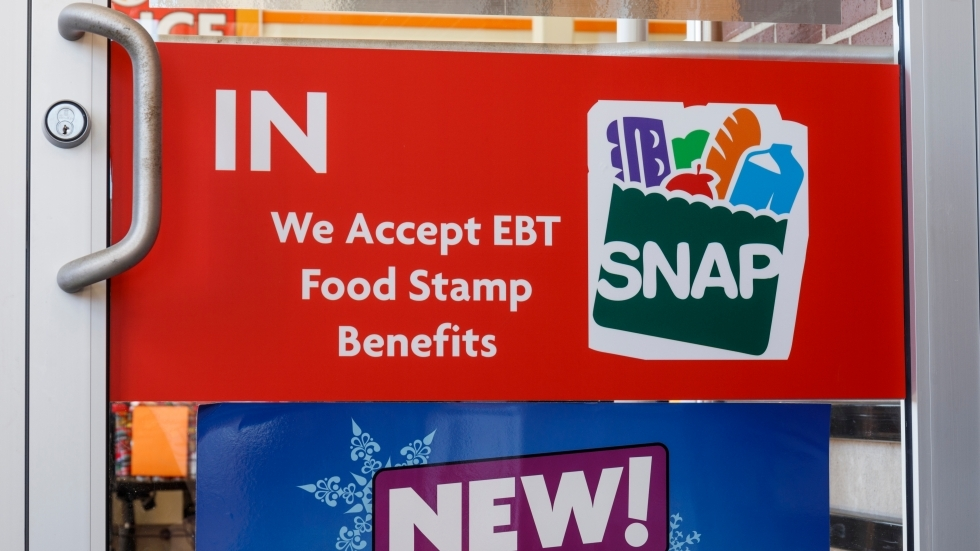 "The entrance of a grocery store with a sign reading ""We Accept EBT Food Stamp Benefits"""