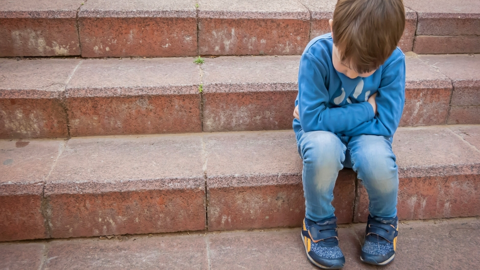 boy sits hunched over on porch steps